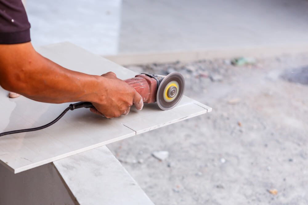 a tiler cutting the end off a white tile with a tile cutting grinder