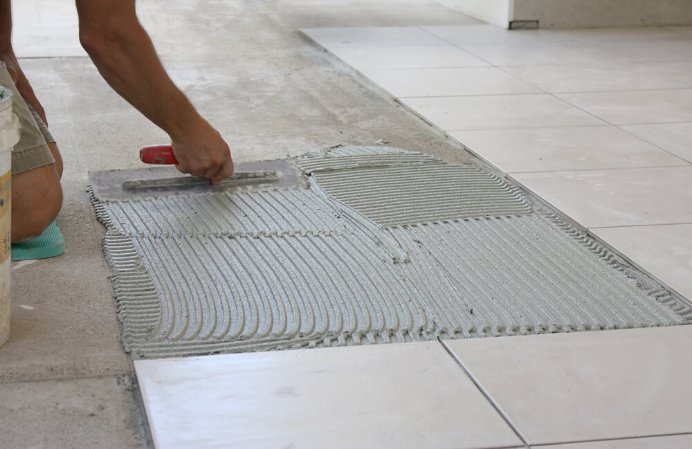 a tiler laying white floor tiles inside of a house using a green knee pad