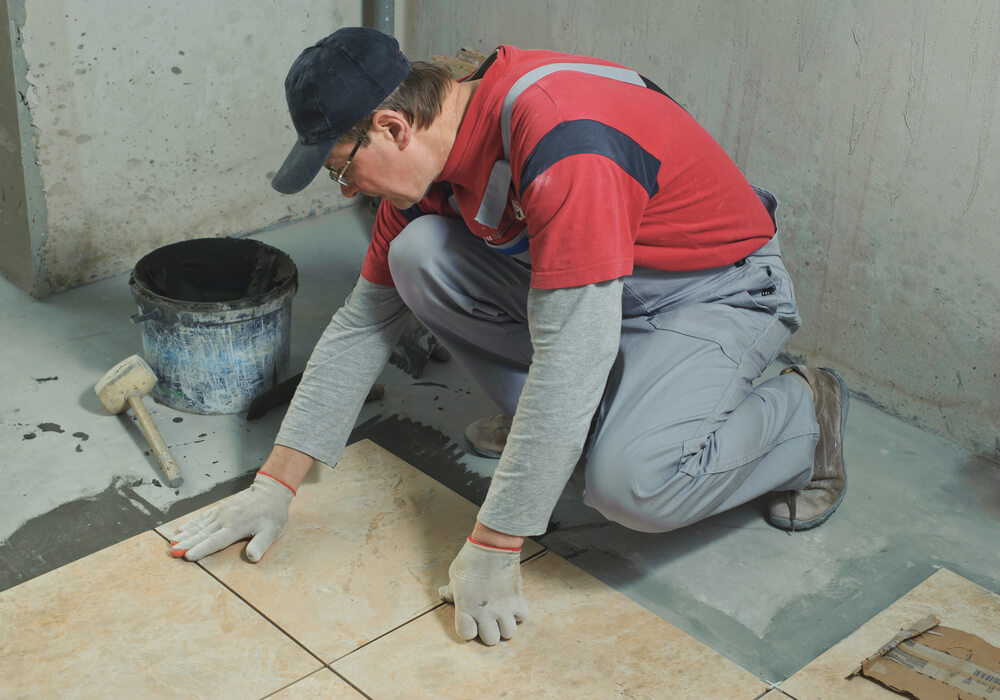a tiler in grey overalls laying a light brown tile with a black bucket next to him and a mallet